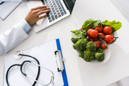 selective focus of vegetables near doctor typing on laptop