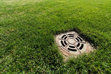 metallic manhole cover on green and fresh grass 스톡 콘텐츠