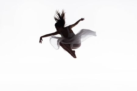 young ballerina in white dress jumping in dance isolated on white