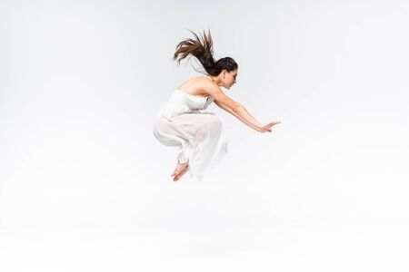 side view of young beautiful ballerina jumping while dancing on grey background
