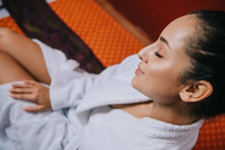 high angle view of attractive woman in bathrobe sitting on massage mat in spa salon