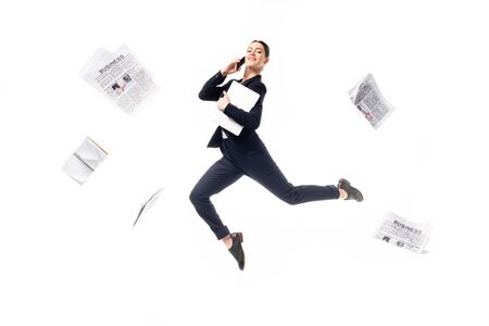 smiling businesswoman talking on smartphone and holding laptop while levitating surrounded with newspapers flying around isolated on white