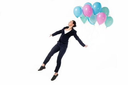 attractive businesswoman in woman levitating with festive balloons isolated on white