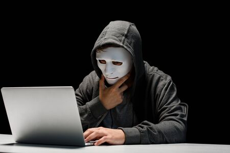 anonymous internet troll in mask typing on laptop keyboard isolated on black Stok Fotoğraf