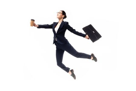 young attractive businesswoman holding coffee to go and briefcase while levitating isolated on white