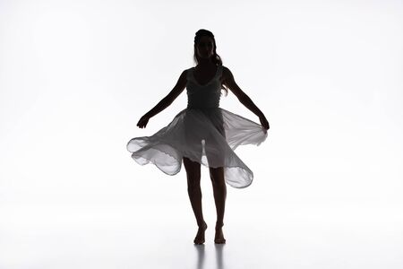 young graceful ballerina in white dress dancing on grey background