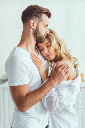 handsome man embracing young beautiful girlfriend in kitchen Banque d'images - 131261554