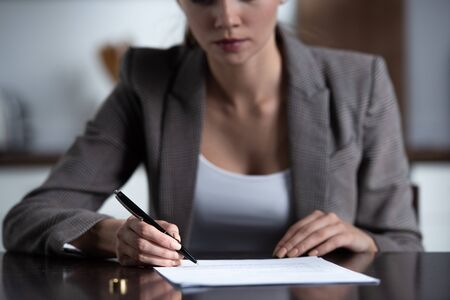 partial view of woman in formal wear signing documents