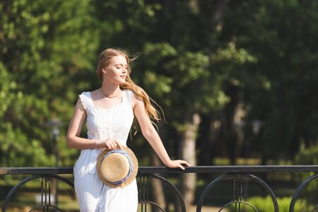 beautiful girl in white dress holding straw hat while leaning on handrail and standing with closed eyes Imagens
