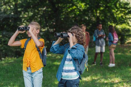 selective focus of happy kids looking through binoculars