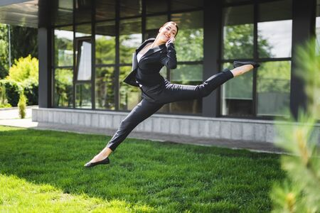 happy businesswoman levitating near office building while talking on smartphone Stock fotó