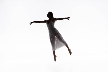 young, graceful ballerina jumping while dancing on white background Reklamní fotografie