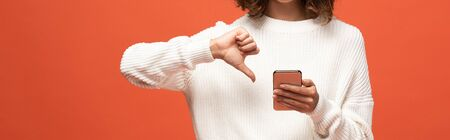 cropped view of woman in autumnal outfit using smartphone and showing thumb down isolated on orange, panoramic shot Foto de archivo - 131261060
