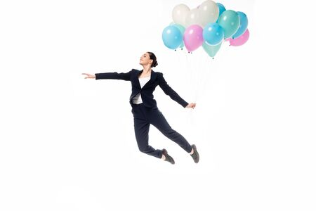 happy businesswoman levitating with festive balloons isolated on white