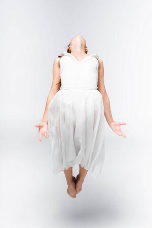 jeune ballerine gracieuse en robe blanche dansant sur fond gris Banque d'images