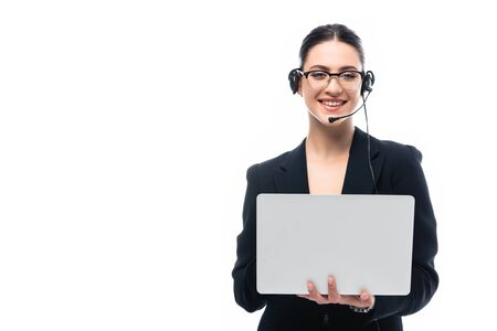 smiling call center operator in headset using laptop while looking at camera isolated on white