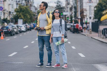 Kobieta trzymająca mapę i stojąca na drodze w pobliżu dwurasowego przyjaciela z plecakiem i aparatem cyfrowym Zdjęcie Seryjne