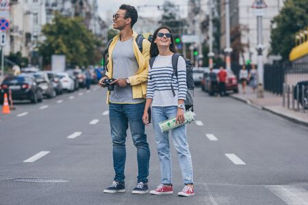 Woman holding map and standing on road near bi-racial friend with backpack and digital camera Stock fotó
