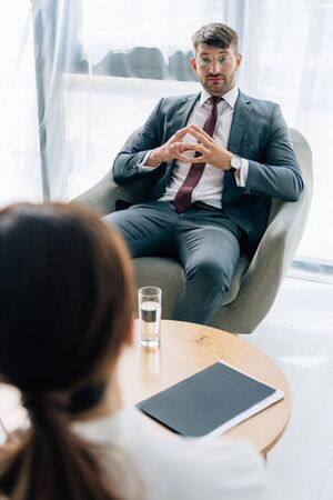 selective focus of journalist talking with handsome businessman in suit and glasses