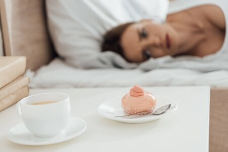 selective focus of suffering woman lying in bed and looking at cupcake
