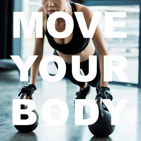 cropped view of girl in sportswear exercising with dumbbells near move your body letters Stockfoto