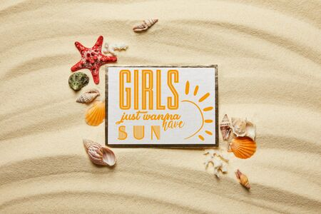 top view of placard with girls just wanna have sun lettering near seashells, starfish and white corals on sandy beach Banco de Imagens