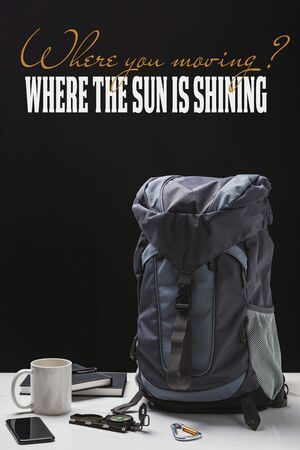 backpack, cup, notebooks, smartphone and trekking equipment isolated on black with where you moving question and where the sun is shining answer