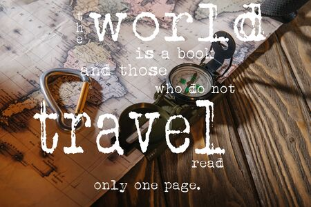 compass, safety hook and map on wooden table with the world is a book and those who do not travel read only one page lettering