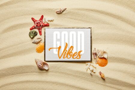 top view of placard with good vibes lettering near seashells, starfish and white corals on sandy beach