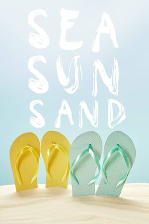summer yellow and blue flip flops in golden sand isolated on blue with sea, sun and sand lettering