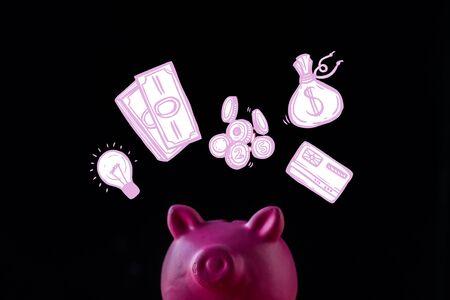 pink piggy bank near light bulb, cash and money bag on black
