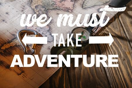 compass, safety hook and map on wooden table with we must take adventure illustration