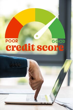 cropped view of businessman pointing with finger at laptop keyboard near credit score letters Фото со стока