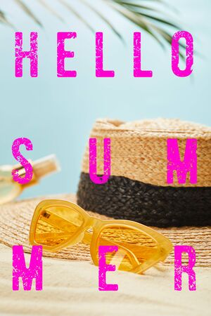 sunglasses near straw hat and bottle with suntan oil on sandy beach isolated on blue with hello summer illustration Stockfoto