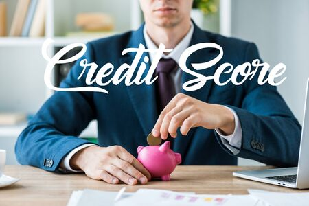 cropped view of businessman putting metallic coin into pink piggy bank near credit score letters