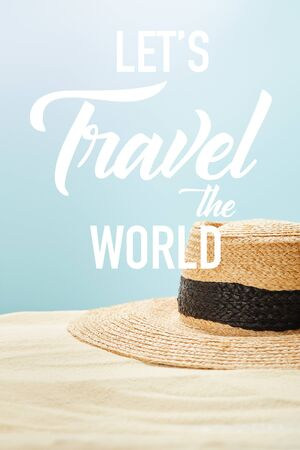 selective focus of straw hat on golden sand in summertime isolated on blue with lets travel the world illustration