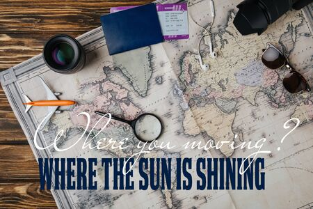 top view of magnifying glass, small model plane, sunglasses, photo camera, lens and passport with boarding pass on map with where you moving question and where the sun is shining answer 스톡 콘텐츠