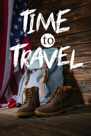 trekking boots, backpack and american flag on wooden surface with time to travel illustration