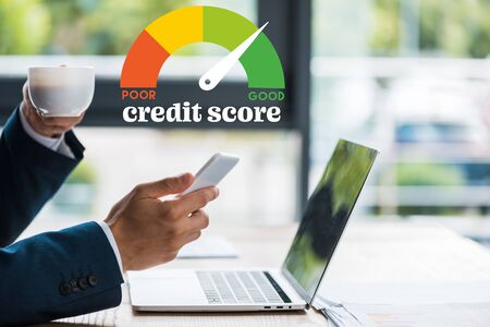 cropped view of man holding smartphone and cup near laptop and credit score letters
