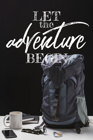 backpack, cup, notebooks, smartphone and trekking equipment isolated on black with let the adventure begin lettering Фото со стока