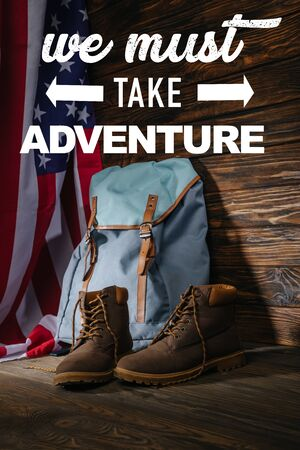 trekking boots, backpack and american flag on wooden surface with we must take adventure illustration