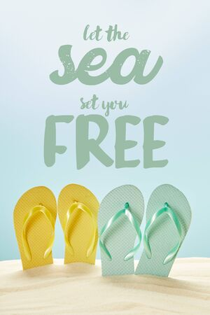 summer yellow and blue flip flops in golden sand isolated on blue with let the sea set you free lettering
