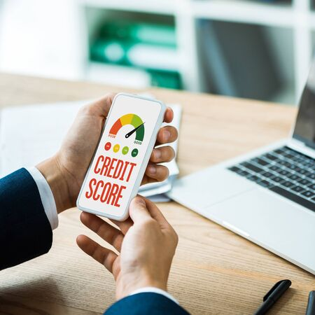 cropped view of man holding smartphone with credit score lettering on screen near laptop and pen on table  Фото со стока