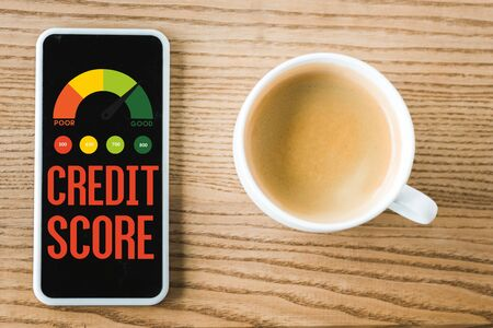 top view of smartphone with credit score lettering on screen near cup of coffee on table Фото со стока - 131314469