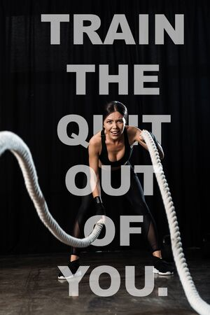 selective focus of sportswoman working out with battle ropes near train the quit out of you letters on black Stockfoto