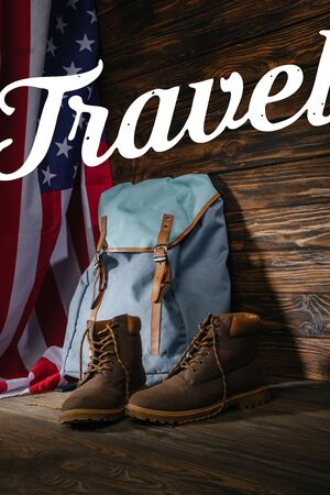 trekking boots, backpack and american flag on wooden surface with travel illustration