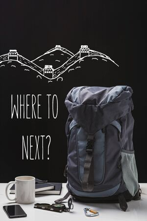 backpack, cup, notebooks, smartphone and trekking equipment isolated on black with where to next question
