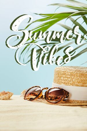 sunglasses near straw hat and seashells in summertime isolated on blue with summer vibes illustration