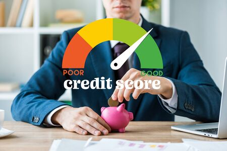 cropped view of businessman putting metallic coin into piggy bank near speed meter and credit score letters