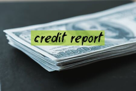 selective focus of stack with dollar banknotes near credit report lettering on black